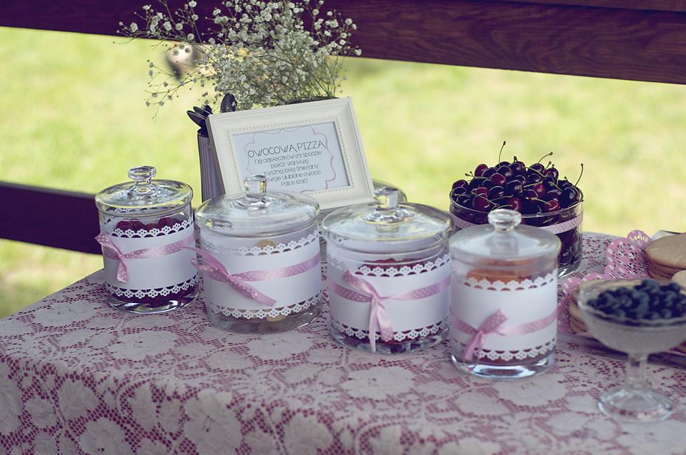 Słoje z owocami i ciasteczkami. Przewiązane ozdobnym papierem i różową tasiemką w kropeczki.