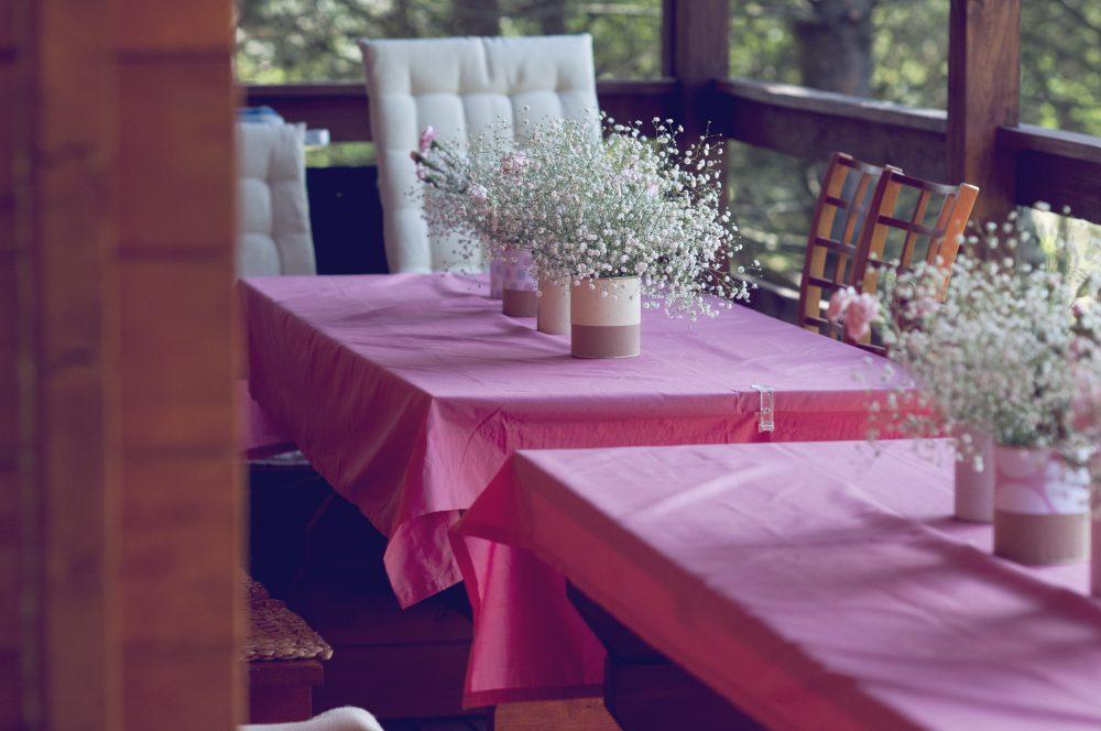 Gipsówka w ozdobnych puszkach. Serwety w kolorze pastelowego różu.