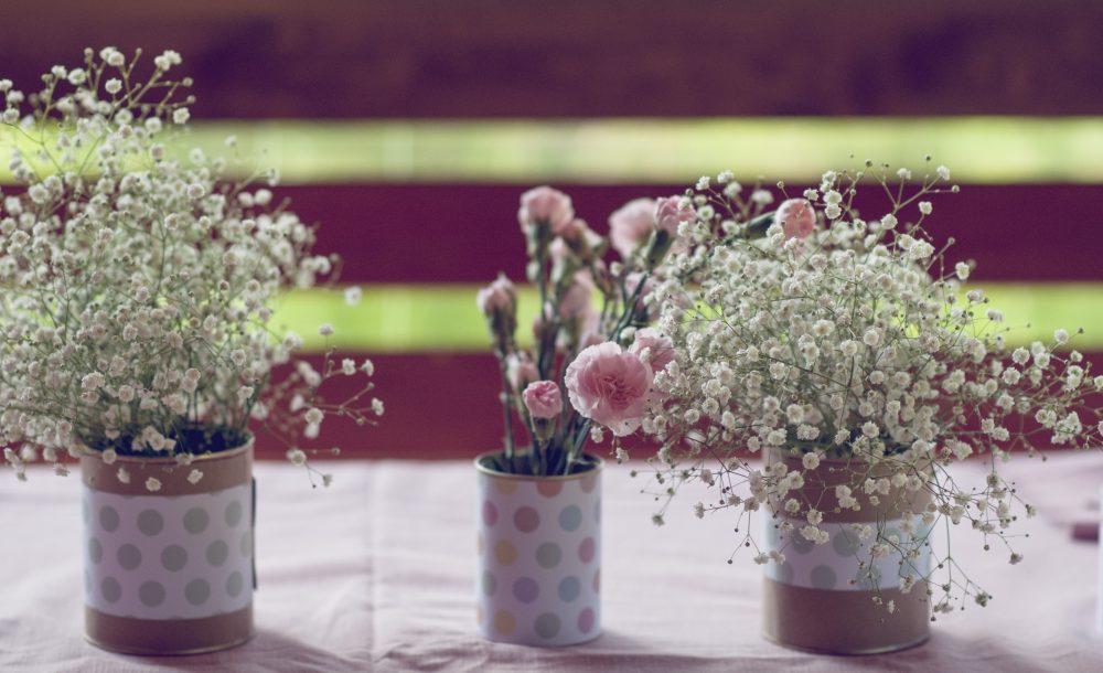 Różowe goździki i gipsówka w puszkach.
