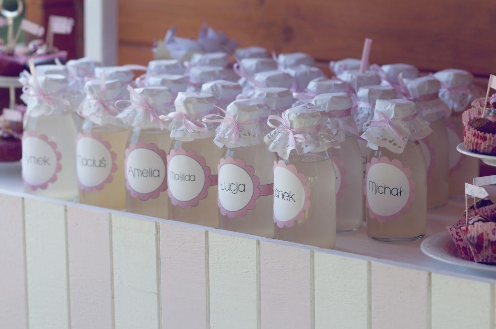 Butelki z lemoniadą z imiennymi etykietami. Papierowe słomki.