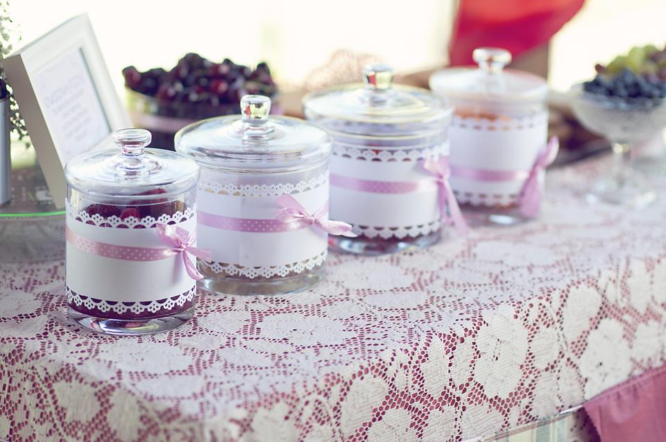 Szklane słoje ześwieżymi owocami. Przyozdbione ażurowym papierem iróżową tasiemką wkropeczki.