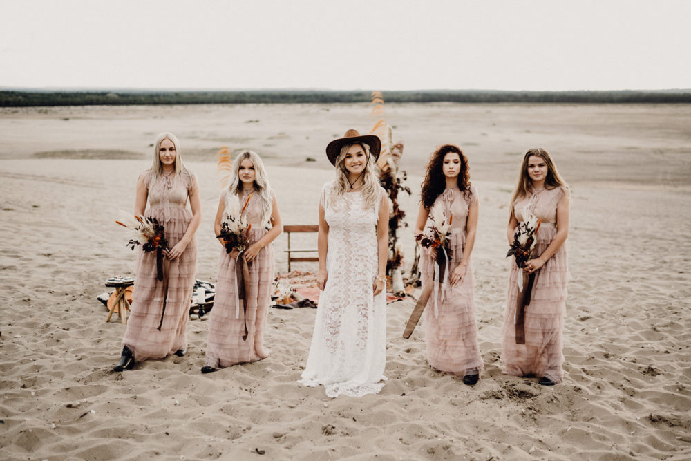 Panna młoda z druhnami w boho sukni ślubnej i kowbojkach.